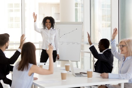 Smiling african american female coach team leader mentor raising hand with happy diverse mixed race people engaging in voting or teambuilding at employees business class training, supporting unity Stockfoto