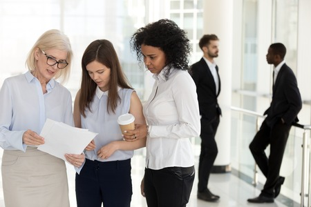 Mature team leader and young female employees discussing paperwork standing in office, diverse employees talking about document, executive giving instructions explaining work to colleagues interns Banque d'images - 112485499