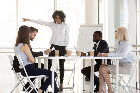 Angry mixed race manager team leader firing incompetent employee intern for bad results asking to leave group office meeting having conflict or dispute, racial discrimination at work concept