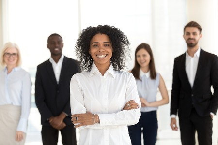 Smiling young african corporate employee executive, mixed race office worker, female black business coach, millennial professional looking at camera standing with diverse team in office, portrait