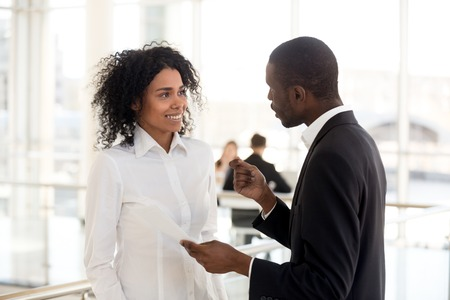 African american mentor ceo explaining helping young smiling mixed race intern with paperwork, black executive talking to employee, colleagues discuss document in office having business conversation Banque d'images - 112485549