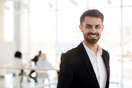 Smiling millennial businessman in suit looking at camera posing in office, portrait of happy confident male ceo, successful entrepreneur, executive leader, company manager, business coach headshot