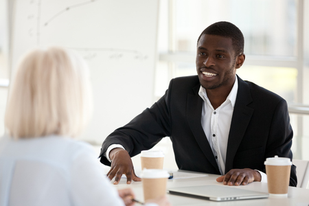 Smiling african american businessman mentor coach in suit speaking at office meeting discussing new project, sharing idea or making business offer to female partner talking to colleague or client