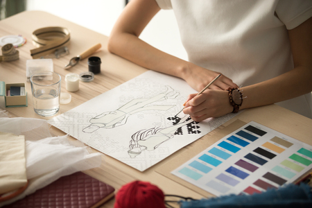 Female clothing designer coloring sketch, drawing with brush at workplace close up in workshop studio, fashion designer, dressmaker creating new fashionable handmade clothes collection, hands view Foto de archivo - 112485583