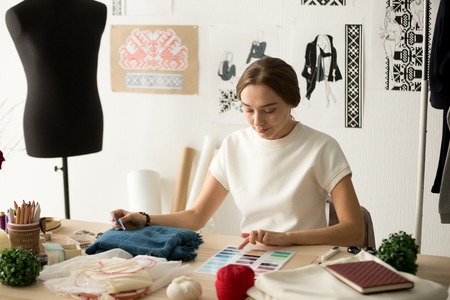 Female clothes designer working with new samples of textile in cozy workshop studio, focused fashion designer, dressmaker choosing colors for fashionable handmade clothes, looking at color palette 写真素材