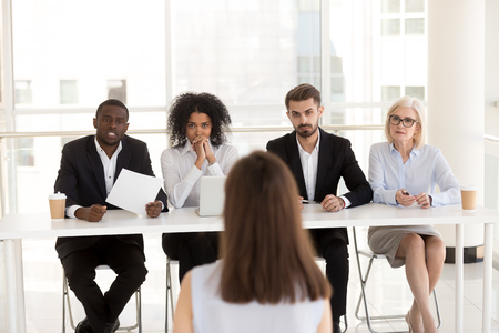Serious focused diverse hr recruiting people group listening applicant performance at job interview, multi-ethnic recruiters team make decision consider hiring seeker thinking about first impression