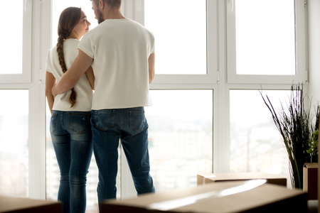 Young loving couple embracing in new apartment with packed belongings in cardboard boxes, thinking about good future in own rental house, beginning live together, looking to each other, rear view