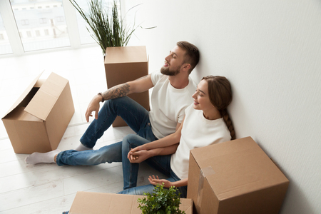 Tired young couple sitting leaning back against wall with closed eyes in new apartment with packaged belongings in cardboard boxes, family just arrived in house, man and woman beginning live together Stock Photo