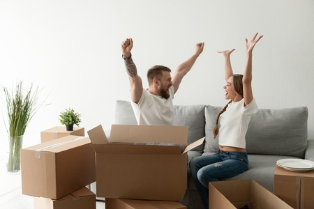 Felice giovane coppia eccitata seduta insieme sul divano, divano che celebra il trasloco nella nuova casa con scatole di cartone con effetti personali, la famiglia è appena arrivata nella nuova casa, l'uomo e la donna iniziano a vivere insieme