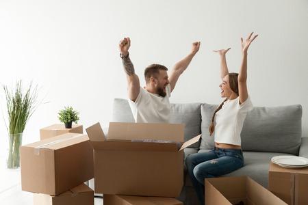 Gelukkig opgewonden jong stel samen zittend op de bank, bank vieren verhuizen naar nieuw huis met kartonnen dozen met bezittingen, familie net aangekomen in nieuw huis, man en vrouw beginnen samen te leven