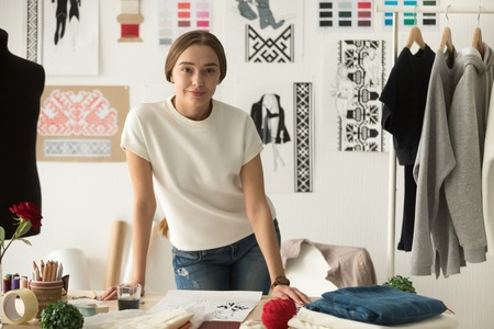 Portrait of confident fashion clothing designer standing at workplace leaning on desktop, talented young dressmaker, tailor shop owner posing in workshop, sewing shop, studio, looking at camera Stockfoto
