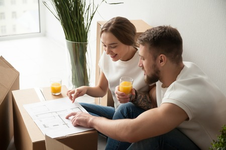 Young smiling couple discussing, pointing at house architectural plan, drinking juice, sitting together, planning new apartment interior design, remodeling, renovation, cardboard boxes with belongings