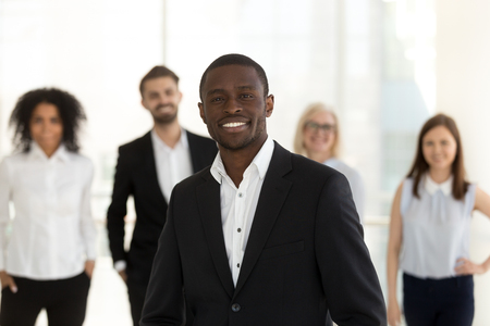 Portrait of smiling confident african american corporate leader or company ceo in suit posing with diverse team, happy professional black business coach, successful male executive looking at camera