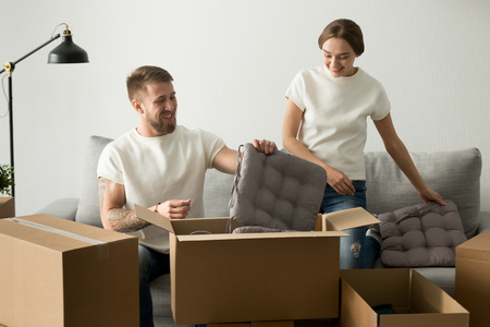 Smiling young couple unpacking cardboard boxes with belongings after moving, laughing wife and husband unboxing together, man and woman beginning live together, rent first apartment, take mortgage