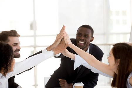Happy african coach and diverse people group giving high five together, motivated office employees celebrating corporate success, unity help support in teamwork, engaging in team spirit concept Archivio Fotografico