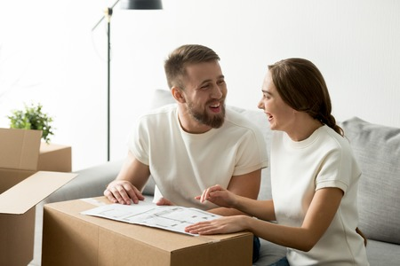 Happy laughing smiling couple discussing house architectural plan, planning new apartment interior design, remodeling, renovation, cardboard boxes with belongings, man and woman having fun together
