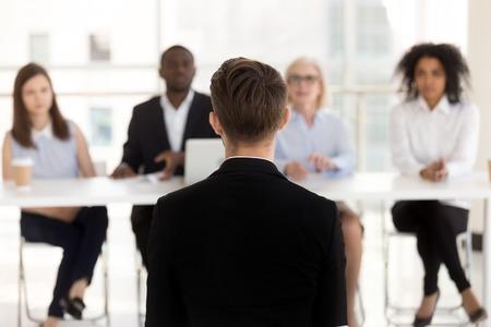 Vista posteriore del candidato in cerca di lavoro durante l'esibizione al colloquio con il team delle risorse umane, il candidato di posto vacante maschile si siede a parlare facendo la prima impressione su reclutatori, risorse umane, concetto di occupazione