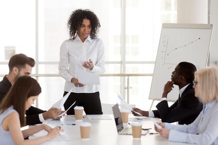 Afroamerikanische Projektmanagerin, die einen Bericht bei diversen Gruppentreffen vorstellt, ernsthafte Teamleiterin gemischter Rassen, die mit Büroangestellten spricht und beim Briefing den neuen Geschäftsplan erklärt