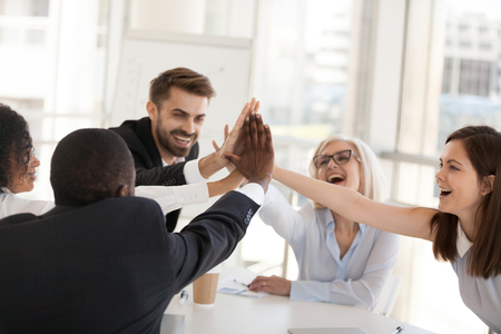 Excited multiracial office associates employees group giving high five engaged in coaching team spirit, motivated by unity, involved in good corporate relations celebrate business success concept