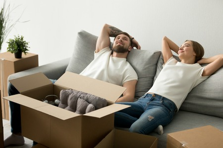 Calm relaxing couple sitting together on couch at new house after moving, family just arrived in new home, man and woman start living together, laying together on sofa, feeling tired after unpacking