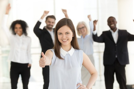 Happy client showing thumbs up satisfied with good service, excited business team people at background, young smiling woman raising finger as concept of best choice approval, recommendation, portrait Banque d'images - 112485800