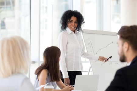 Smiling mixed race mentor gives presentation at diverse team office training explains sales growth graph on flipchart, friendly african american coach speaking about good work result at group meeting