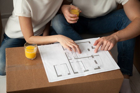 Young  couple discussing house architectural plan, drinking juice, sitting together, planning new apartment interior design, remodeling, renovation, cardboard boxes, close up, hands view