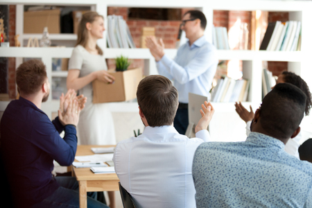 Smiling happy team leader with colleagues applauding to just hired female employee, office workers welcoming new member of team, happy woman holding box with belongings, first day at work concept