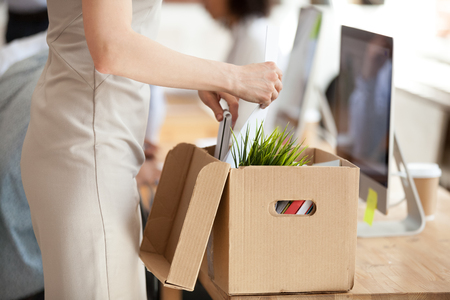 New female employee, trainee, intern unpacking box with belongings at shared workspace, just hired worker pulling things out of open box, preparing for first day at work concept close up Stok Fotoğraf - 114275862