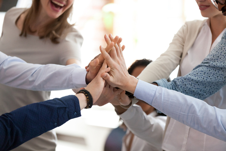 Excited happy multiracial team giving high five, celebrating good results, congratulating with success at briefing, group of employees rejoicing at achieved goal, good teamwork, collaboration, close up