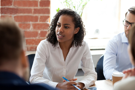 African American woman speaking, offering ideas at company meeting, briefing, female employee expressing opinion, talking with boss, coach, mentor, participating in team building activity