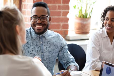 Homme d'affaires afro-américain souriant lors d'un briefing, formation commerciale, réunion d'entreprise, discussion sur la stratégie commerciale, nouveau projet, bons résultats, recevoir des nouvelles amusantes, parler avec une patronne Banque d'images