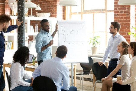 Confident smiling African American business coach speaking presentation to colleagues group at briefing, company meeting, explaining growth of sales graph, reporting about good result, motivating workers Stock Photo