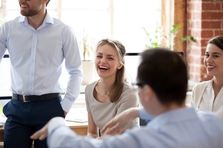 Happy laughing businesswoman at briefing, company meeting with group, team colleagues, office workers brainstorming together, discussing funny news, celebrating good results, good relationships in team