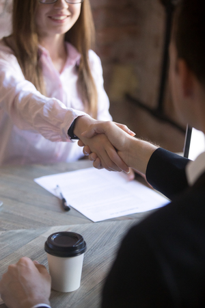 Friendly attractive young woman handshaking man at meeting. Deal with good result, start of work with business partner or customer, good relationship, recruitment, hiring process, HR concept. Close up Stock Photo