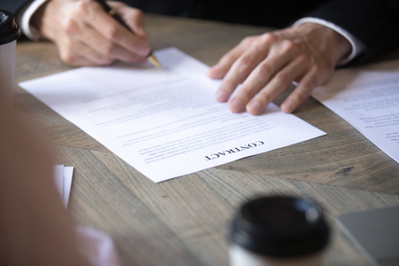 Man in suit fills name form and signs contract with a business partner, employment contract. Client signs the contract. Recruitment, hiring process, close up view Фото со стока