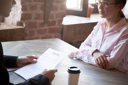 HR manager asks questions about resume to female applicant. Man in suit holds job interview with young woman. Hiring, staff recruiting process. Close up.