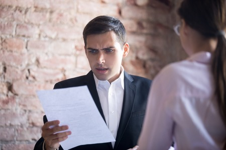 Funny HR manager is dissatisfied with resume of female applicant. Skeptic man is unpleasantly surprised by no good candidate cv. Failed interview. Hiring, staff recruiting process, scam Stock Photo