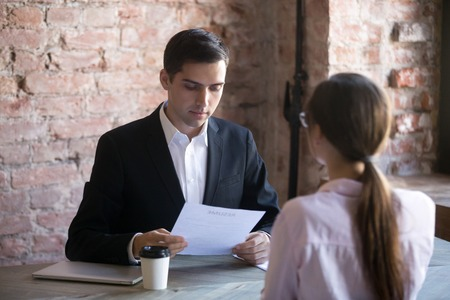 Calm HR manager carefully reading resume of female applicant. Man in suit holds job interview with young woman. Hiring, staff recruiting process.