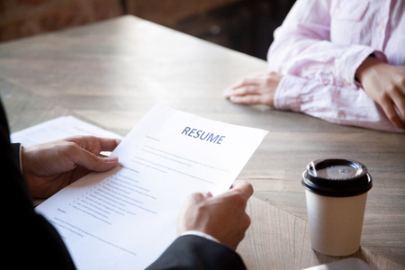 HR manager reading resume of female applicant. Man in suit holds job interview with young woman. Hiring, staff recruiting process. Close up, hands view. Stock Photo