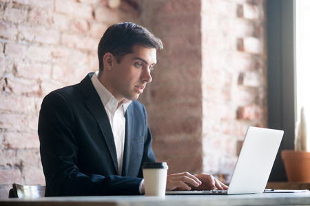 Shocked businessman looking at laptop screen. Unpleasantly surprised employee after receiving bad news. Confused man in suit is reading or typing email 版權商用圖片