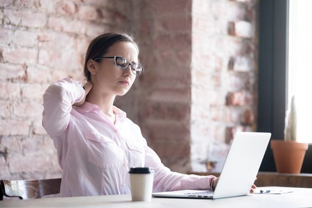 Tired businesswoman massaging strained neck muscles. Young woman experiences discomfort after long work at computer. Uncomfortable workplace. Stock fotó