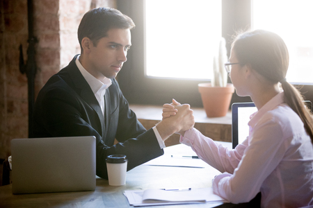 Young man and woman are engaged in arm wrestling, deciding who is stronger at work. Businessman and businesswoman are fighting for leadership, feminism, equal rights concept, eye-to-eye contact Stock Photo