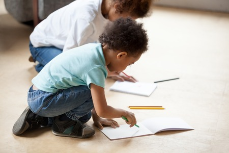 Little African American children drawing with colorful pencils, sitting on floor, cute toddler boy coloring with preschooler sister, playing with sister, siblings spending time together
