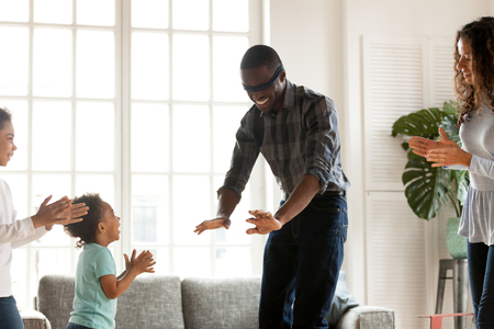 Happy African American family playing hide and seek at home in living room, smiling father with eyed blindfolded trying catch toddler son, little preschooler daughter or attractive wife, having fun