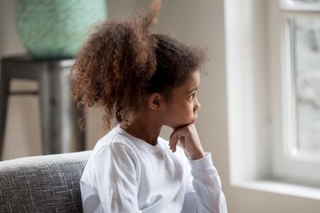 Niña preescolar afroamericana seria pensativa mirando en la ventana, niño pensativo sentado en casa, tomarse de las manos debajo de la barbilla, soñando, mirando en la distancia, sintiendo aburrimiento, teniendo preguntas