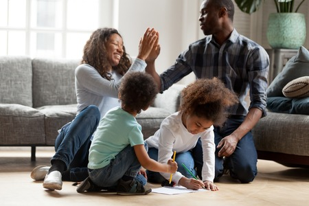 Happy African American family playing together indoors, adorable toddler son and littler preschooler daughter drawing with colorful pencils, smiling joyful wife and husband giving high five 写真素材
