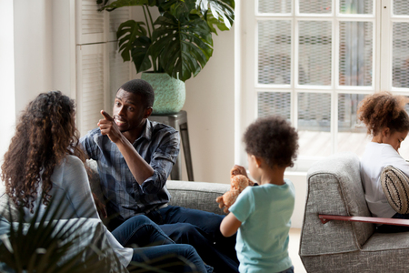 Unhappy African American couple quarrelling at home, sitting on couch in living room, man blaming woman, sad frustrated preschooler girl sitting alone, toddler son with toy in hands, break up family