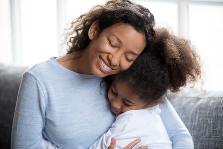 Liefdevolle Afro-Amerikaanse moeder omarmen met peuter schattig dochtertje, samen zittend op de bank thuis, warme relaties ouder en kind, nabijheid, liefde en ondersteuning concept