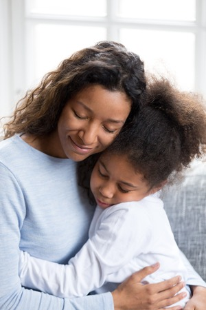 Loving African American mother embracing with preschooler little adorable daughter, sitting together on couch at home, warm relationships parent and child, closeness, love and support concept vertical Stock Photo - 114276747
